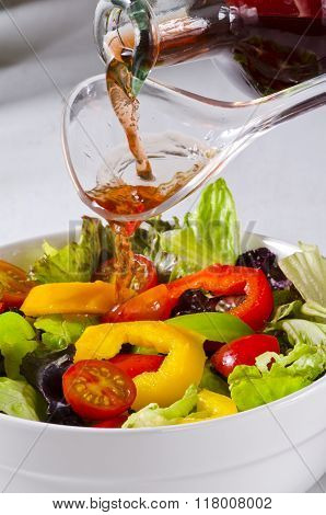 Vinegar Pouring Into Salad Bowl