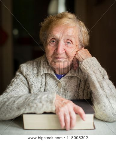 Portrait of elderly woman sitting with book.