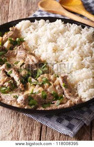 Beef Stroganoff Garnished With Rice Close-up On A Plate. Vertical