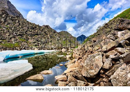 Slope Of Boulders At The Water With Pieces Of Ice Melting Siberian Summer . Eastern Sayan Mountains