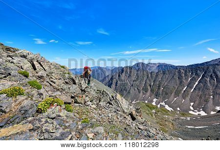 Pass Hopping. Woman With A Backpack On Background Of Mountain Peaks High In  Mountains . Eastern Say