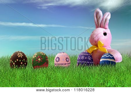 Painted Easter eggs and pink bunny on grass on sky background