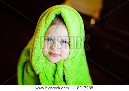 Child With Green Fleece Blanket On His Head On A Dark Background