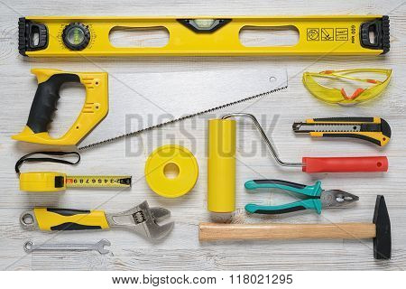 Top view of construction instruments and tools on wooden DIY workbench. Level, saw, glasses, tape me