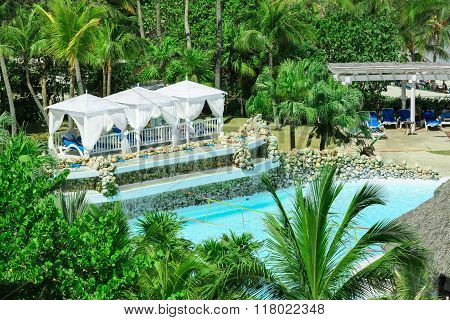 Great comfortable white gazebos near the pool in tropical palm trees garden