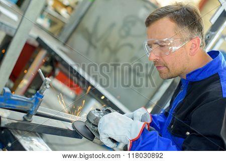 Workman using angle grinder