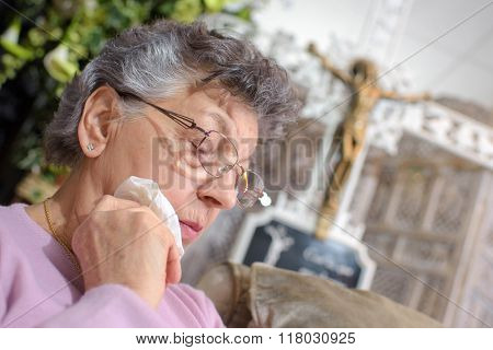 elderly woman with a crucifix in the backgroud