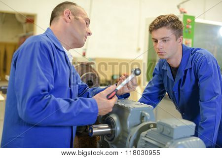 Man talking to apprentice, holding socket wrench