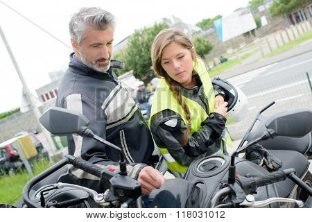 Young lady looking at motorcycle with older man