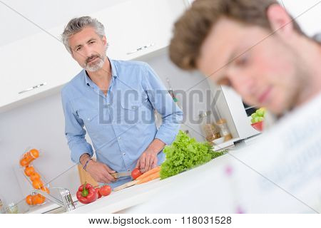 Man cooking, looking towards younger man holding book