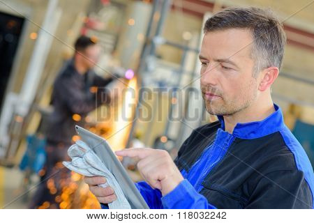 Workman holding gloves, using touchscreen tablet