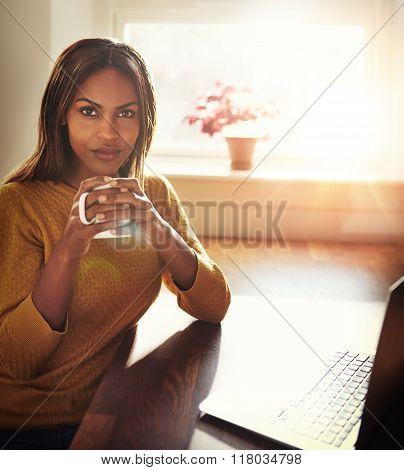 Woman Holding Coffee While Seated Near Window