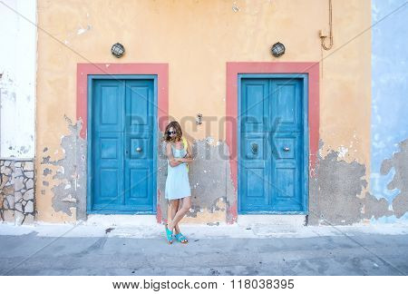Yound blond woman at typical greek traditional town with colorful buildings on Kastelorizo Island, G