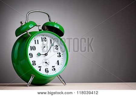 Big green alarm clock on grey background