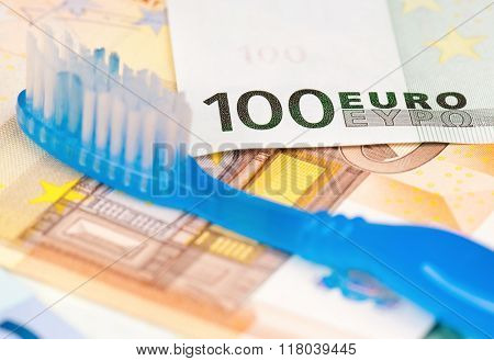 Close-up of tooth brush on heap of euro