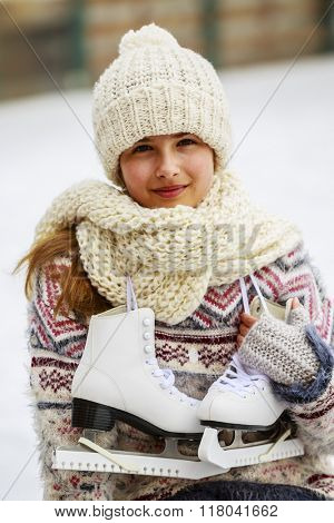 Winter sport, girl with a pair of ice skates