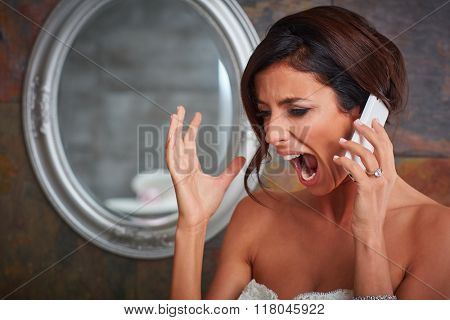 Closeup photo of young bride shouting on mobilephone.
