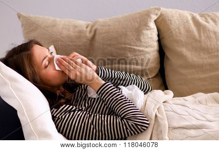 Portrait of a sick woman blowing her nose while sitting on the sofa