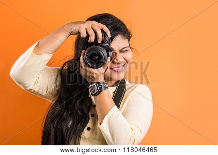 Young beautiful indian woman taking a photo with a digital camera, asian girl with camera, indian gi