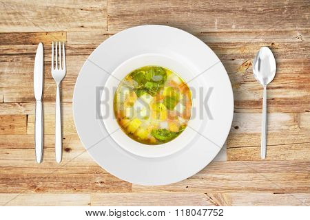 Minestrone Soup In White Plate With Knife, Fork And Spoon On Wooden Table