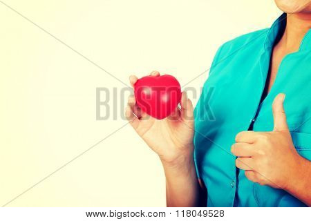 Young female doctor or nurse holding heart toy