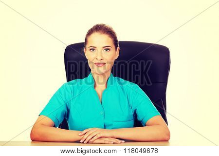 Young female doctor or nurse sitting behind the desk