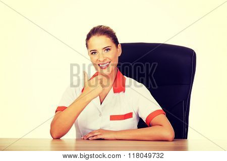 Female doctor sitting behind the desk and shows thumb up