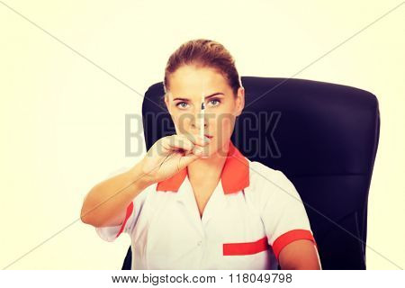 Female doctor sitting behind the desk and holding syringe