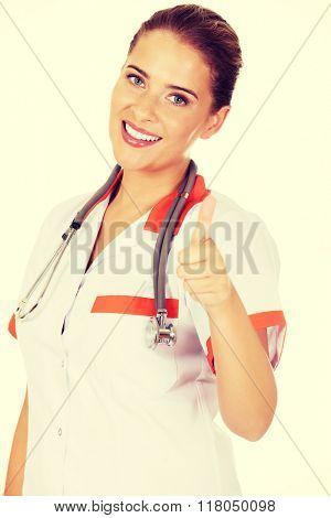 Young smile female doctor or nurse shows thumb up