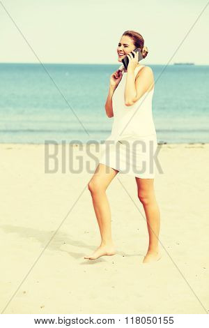 Young elegant beautiful woman talking on the phone on the beach