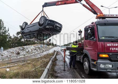Thessaloniki Greece - January 18 2016: Man towing damaged car over a tow truck on the side of the road in Thessaloniki Greece.