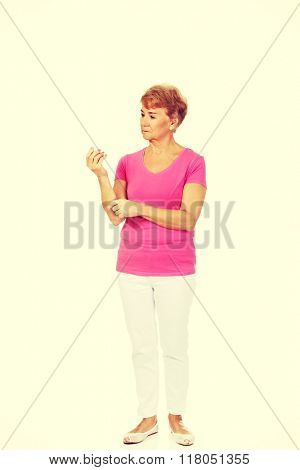 Senior woman holding medicament bottle
