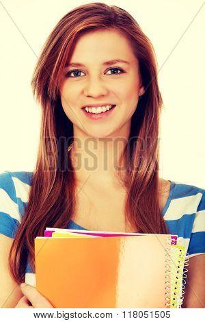 Teenage woman holding a few notebooks
