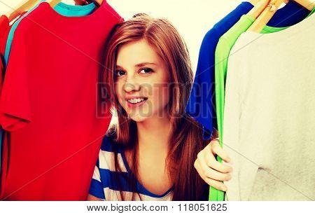 Happy teenage woman between clothes on hanger