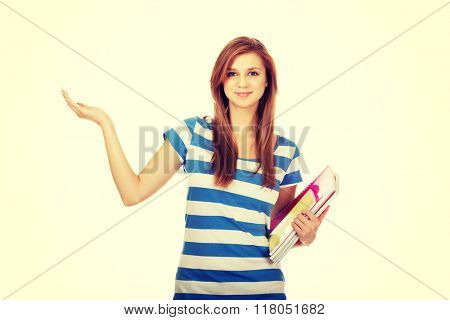 Happy teenage woman presenting something on open palm