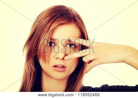 Teenage woman with victory sign on eye