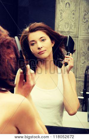 Brunette woman brushing her hair.