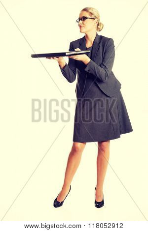Businesswoman standing and holding a laptop
