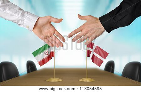 Iran and Denmark diplomats shaking hands to agree deal