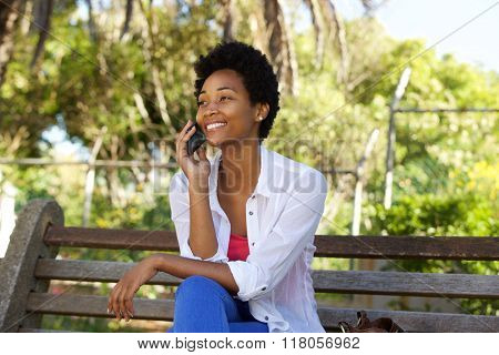 Young Woman On A Park Bench Talking On Mobile Phone