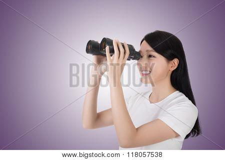 woman using binoculars, studio shot portrait