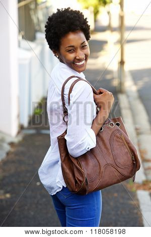 Beautiful Young Woman Walking Along A Street With A Purse