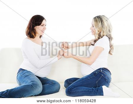 Two beautiful pregnant women holding hands to support each other.