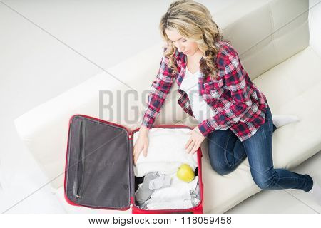 Young attractive pregnant woman packing children's wear to go to maternity clinic.