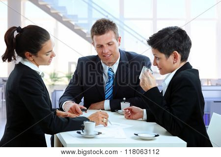Young caucasian business people meeting at office table, drinking coffee. Suit and tie, sitting, smiling, looking at papers.