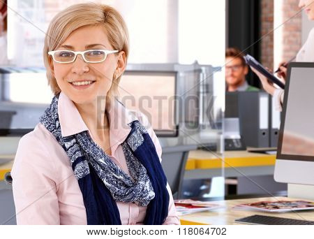 Happy casual caucasian blonde businesswoman at business office, wearing glasses, smiling, looking at camera.