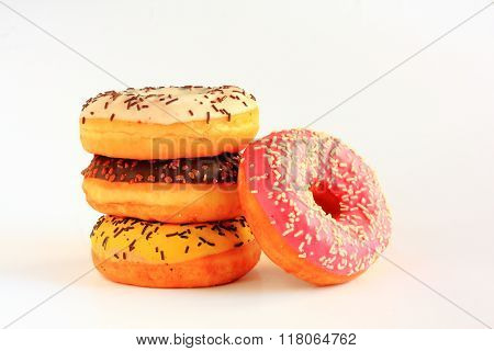 Four Donuts With Yellow, Brown, White And Red Icing