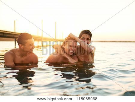 Three Young Boys Playing In A Lake