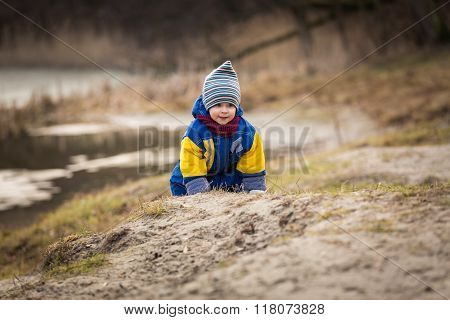 Little Boy Playing On Lake Shore