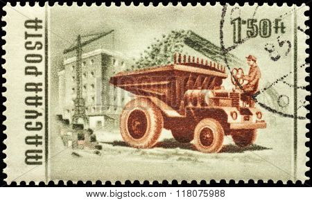 Dump Truck In A Construction On Postage Stamp